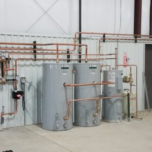 Water heater and storage tanks for emergency eye wash(s) in adjacent building